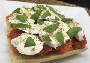 French Bread Pizza - Topping with mozzarella & herbs (Photo by Viana Boenzli)