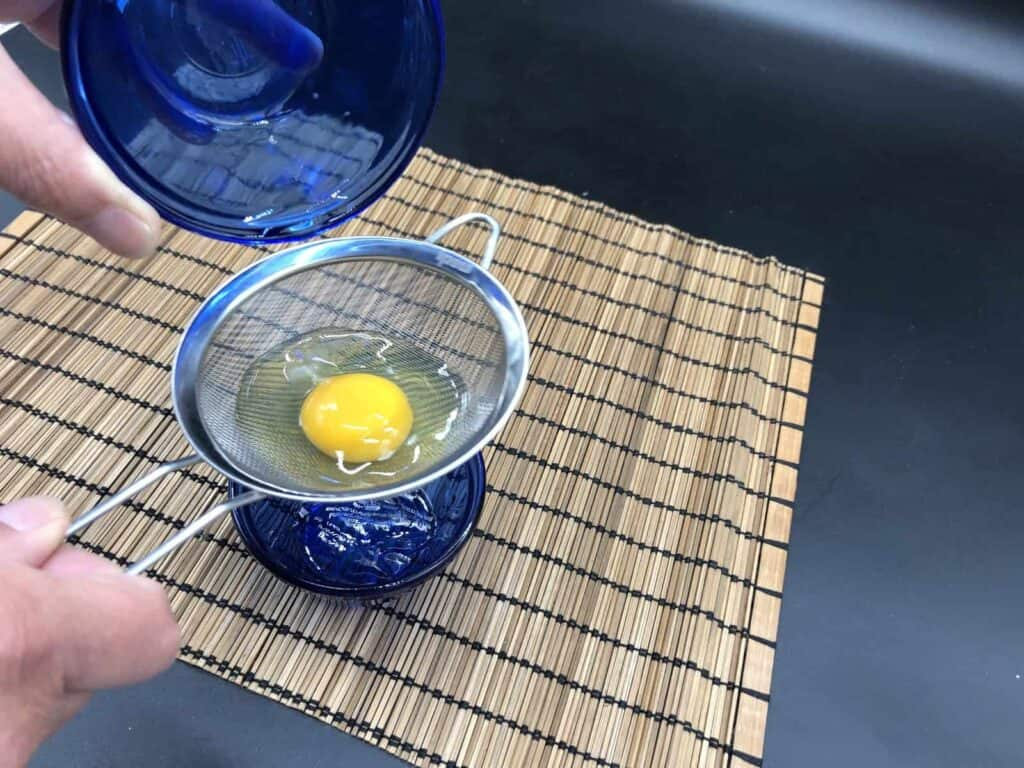 Poached Eggs - Straining the Egg Whites (Photo by Erich Boenzli)