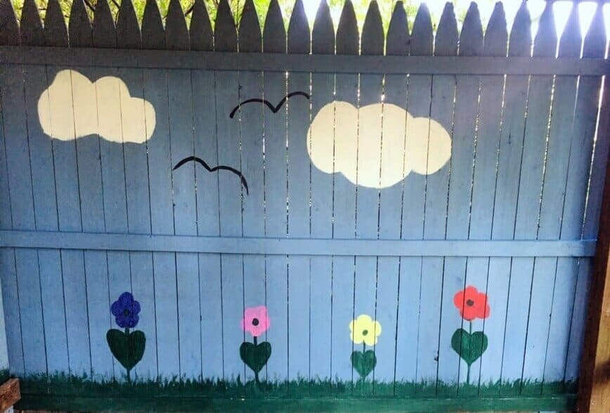 """Painted Fence - Puffy white clouds, """"M"""" birds, and colorful flowers (Photo by Viana Boenzli)"""